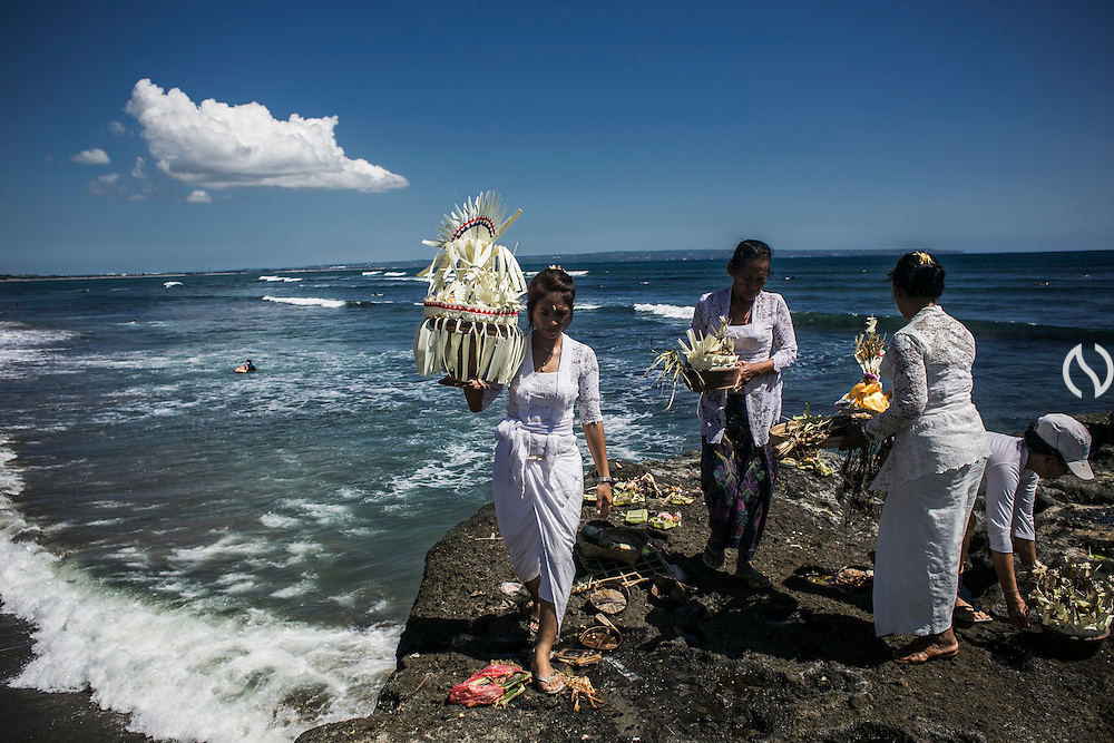 BALI, INDONESIA; MARCH 18, 2015: Balinese Hindu devotees deliver offering to the sea during Melasti, a cleansing ritual before entering Silent Day in Batubolong Beach, Bali, Indonesia on Wednesday, March 18, 2015.
