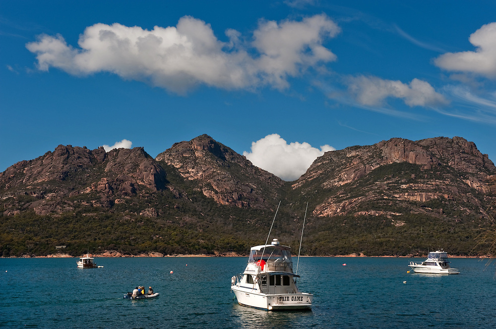 Private motor yachts anchored at Coles Bay with hills in the background in the Freycinet National Park, Tasmania.