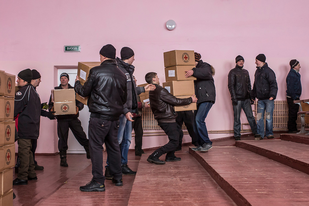 MNOGOPOLYE, UKRAINE - JANUARY 24, 2015: Local residents help unload a delivery of humanitarian aid by the International Committee of the Red Cross in Mnogopolye, Ukraine. ICRC aid deliveries are planned for the area approximately once per month, and supply food and hygiene items for more than one thousand people. CREDIT: Brendan Hoffman for The New York Times