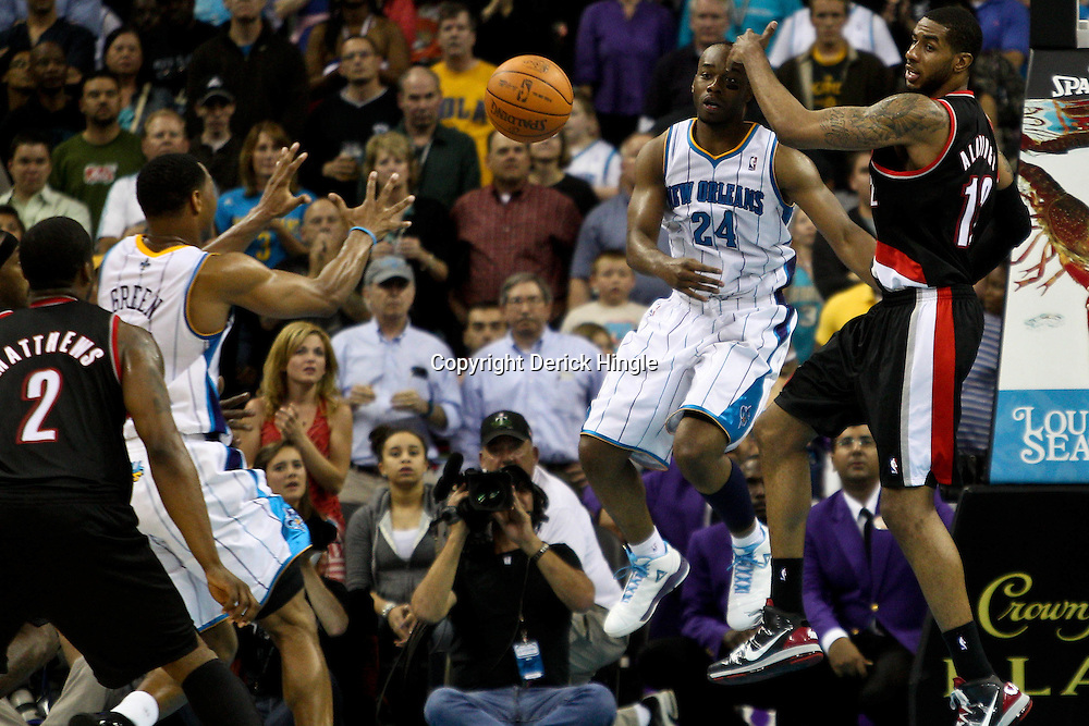 March 30, 2011; New Orleans, LA, USA; New Orleans Hornets power forward Carl Landry (24) passes to New Orleans Hornets shooting guard Willie Green (33) as Portland Trail Blazers power forward LaMarcus Aldridge (12) defends during the fourth quarter at the New Orleans Arena. The Hornets defeated the Trail Blazers 95-91.   Mandatory Credit: Derick E. Hingle