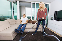 Woman vacuuming while man play video game in living room at home