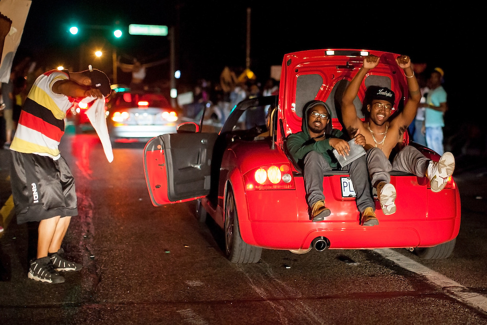 A man, with two people sitting in his trunk, ghost-rides down West Florissant Avenue in Ferguson. Protests have been ongoing in Ferguson, Missouri since the shooting death of Michael Brown, the eighteen-year-old unarmed teen killed by police on August 9, 2014.