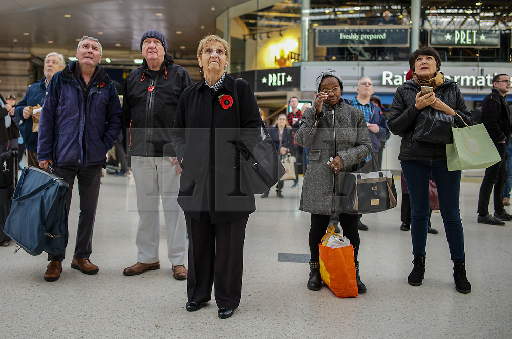 © Licensed to London News Pictures. 11/11/2019. London, UK. A group stand still for the two minute silence at Waterloo Station before their train journey. Hundreds of people around the UK respect the two minute silence for Armistice Day today. Photo credit: Alex Lentati/LNP