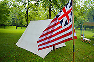 8/18/12 11:44:32 AM - Warwick, PA. -- A flag flies as a tent rests in tha background during a revolutionary war reenactment at the Moland House August 18, 2012 in Warwick, Pennsylvania. -- (Photo by William Thomas Cain/Cain Images)..