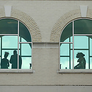 Guests watch the crowds from the windows above the main entrance at the 138th running of the Kentucky Derby at Churchill Downs in Louisville, Ky. Saturday May 5, 2012.  Photo by David Stephenson