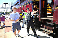 LANSDALE, PA - AUGUST 24: Conductor Wayne Whiteley  ® of Langhorne, Pennsylvania directs passengers to the New Hope and Ivyland Railroad during Founders Day August 24, 2013 in Lansdale, Pennsylvania. The New Hope and Ivyland Railroad made special trips as part of Founders Day from Lansdale to Souderton. (Photo by William Thomas Cain/Cain Images)