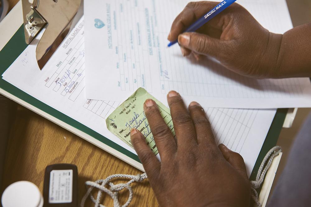 INDIVIDUAL(S) PHOTOGRAPHED: N/A. LOCATION: Sacré-Cœur Hospital, Milot Commune, Cap-Haïtien, Haïti. CAPTION: In the emergency room at Sacré-Coeur Hospital, a nurse writes notes in a patient's file.