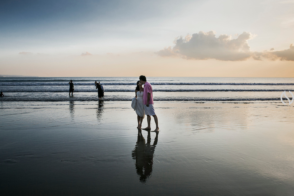 BALI, INDONESIA; MARCH 27, 2015: A couple from China kisses during pre-wedding photo session at Double Six beach, Bali, Indonesia on Friday, March 27, 2015.