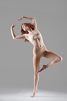 Dancer stands on one leg stretching arms above head