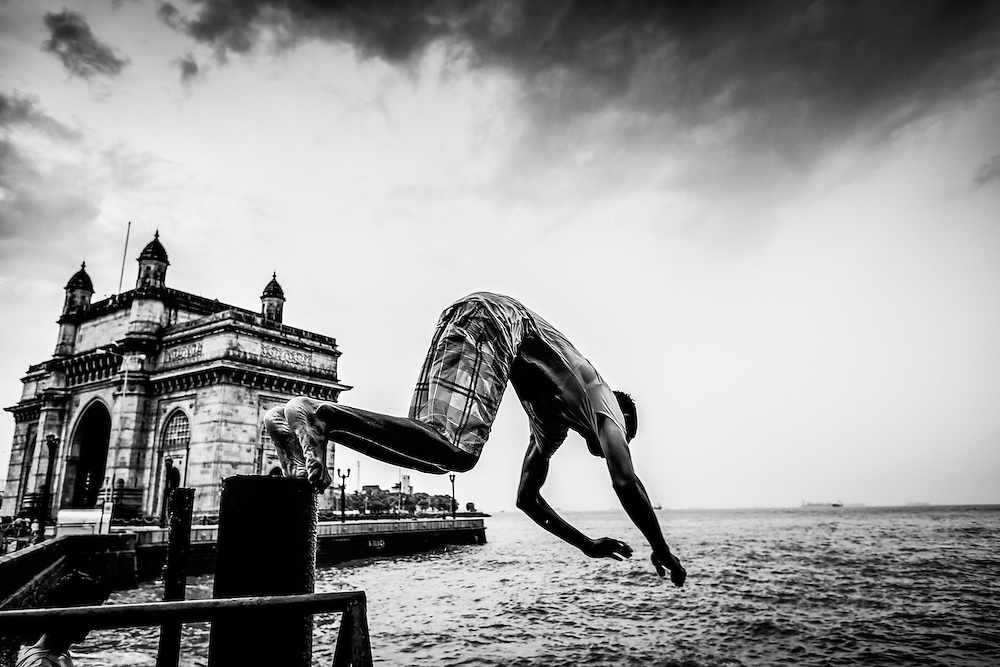 A man dives in front of the Gate of India, Mumbai.