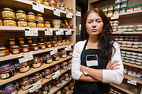 Portrait of confident saleswoman standing arms crossed in grocery store