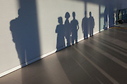 The silhouettes of airport passengers against a wall in the terminal as they have disembarked from their flight, on 10th July 2016, at Lisbon, Portugal. Several people are in a line next to each other, their outlines defined and their shadows stretching across the terminal floor. (Photo by Richard Baker / In Pictures via Getty Images)
