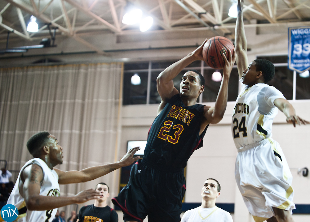 Hickory's Denzel Dillingham goes up for a shot against Concord's Darren Black and Jacquise Moore during the regional round of the NCHSAA 3A playoffs Thursday night at the University of North Carolina at Greensboro. Hickory won the game 95-82 to end the Spiders season. (Photo by James Nix)