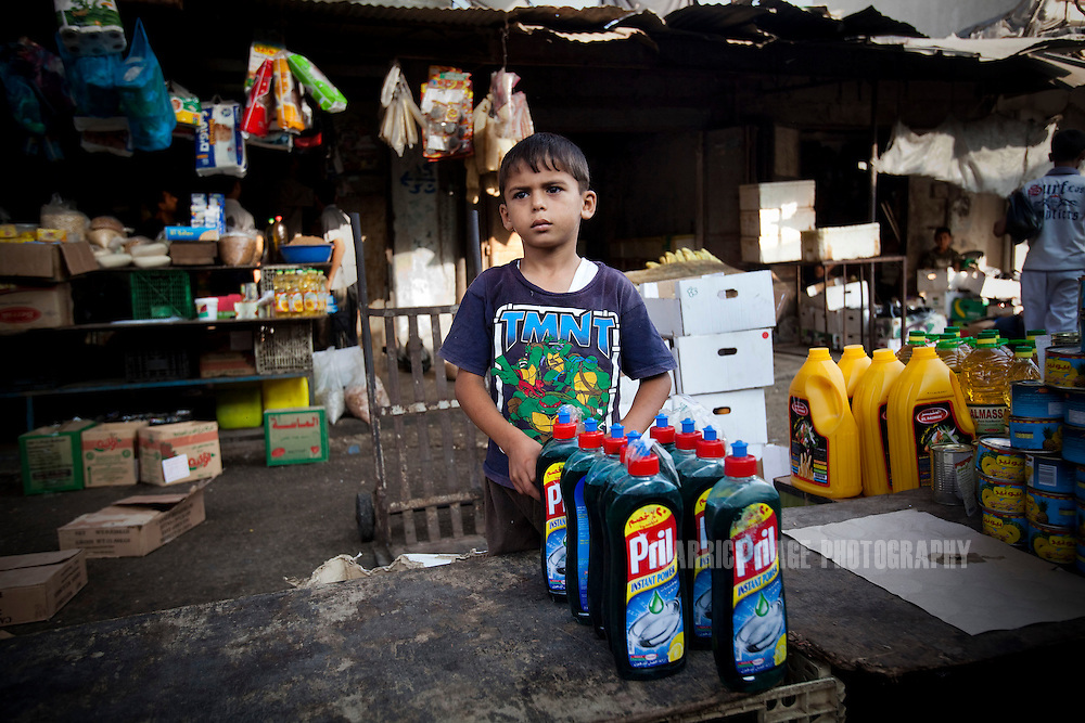 GAZA CITY, GAZA STRIP - JULY 9: A Palestinian boy waits for customers at Fras Market, on July 9, 2010, in Gaza City , Gaza Strip. With Gaza's economy devastated by years of sanctions and decades of conflict, many families send their children to work. Although Israel eased its blockade in mid-June - allowing in consumer goods - little has changed for Gaza's poorer families. Unemployment runs at 40% and the majority of the population is dependent upon aid handouts for their basic needs.  (Photo by Warrick Page)