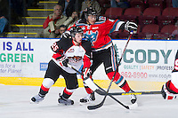 KELOWNA, CANADA - DECEMBER 8:  Madison Bowey #4 of the Kelowna Rockets checks Joseph Carvalho #25 of the Prince George Cougars at the Kelowna Rockets on December 8, 2012 at Prospera Place in Kelowna, British Columbia, Canada (Photo by Marissa Baecker/Shoot the Breeze) *** Local Caption ***