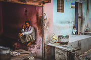 A man resting in his workshop while his son is playing outside, Jaipur, India 2013