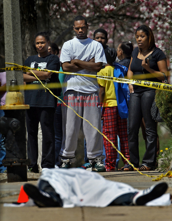 Shocked neighbors and friends stand on Homestead Street in Boston shortly after 18 year old John Davis was shot dead in front of his home.