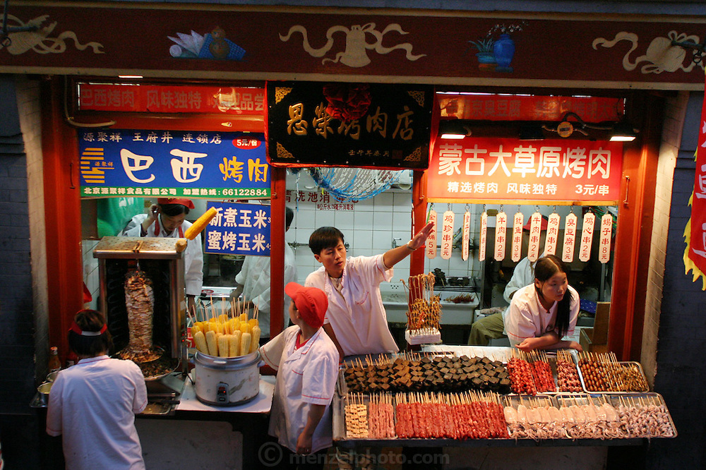 "Chinese cities are among the world capitals of street food, with stands selling an extraordinary variety of treats. In central Beijing, the Enrong Roasted Meat Store offers ""Brazilian roasted meat"" (left foreground, the vertical, rotating stack of meat), ""fresh-boiled"" and ""honey-roasted"" corn on the cob, ""Mongolian grasslands roasted meat,"" dry, tire-black ""stinky tofu,"" and a rack of skewered scorpions (under salesman's outstretched arm). Hungry Planet: What the World Eats (p. 77). This image is featured alongside the Dong family images in Hungry Planet: What the World Eats."