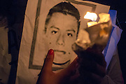 Protestor carrying a candle and a portrait in favor of the forty three missing students in Iguala, Guerrero.