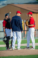 KELOWNA, BC - JULY 17: Jake Fischer #19, Zach Jacobs #27 and the Kelowna Falcons' coach stand on the pitchers mound against the Wenatchee Applesox at Elks Stadium on July 17, 2019 in Kelowna, Canada. (Photo by Marissa Baecker/Shoot the Breeze)