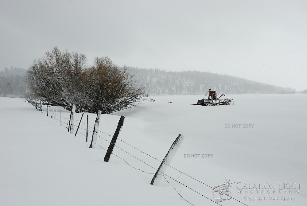 Winter brings snow to this farm field near Klamath Falls, Oregon with an old piece of farming equipment in the distance.