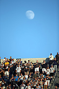 A crowd of fans listens to the National Anthem as the blue sky frames the moon before the San Diego Chargers 2014 NFL preseason football game against the Dallas Cowboys on Thursday, Aug. 7, 2014 in San Diego. The Chargers won the game 27-7. ©Paul Anthony Spinelli