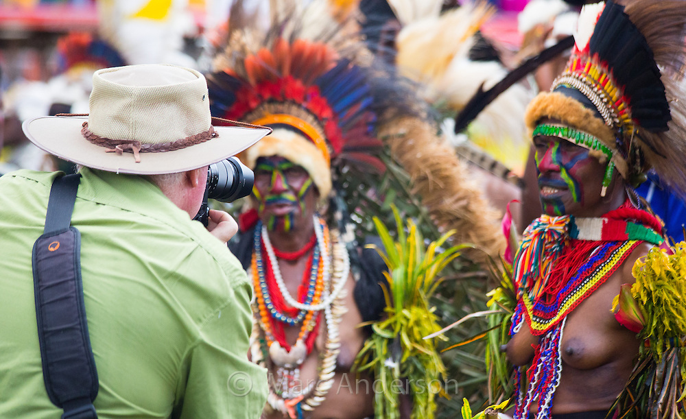 Tourist taking photos of local tribespeople at the Goroka Show in Papua New Guinea.