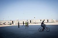 "HAL FAR, MALTA - JUNE 21: Immigrants play ball and ride bikes at the Hangar Open Center in Hal Far (which translates as ""Rat's Town"") on June 21, 2011. The Hangar Open Center is a field with an ex-aircraft hangar which includes Swiss Red Cross tents in a dark, non lit space, and external containers. The conditions are very poor and the has inflamable oil on the floor.<br /> <br /> The Open Centres in Malta serve as a temporary accomodation facility, but they ended becoming permanent accomodation centres, except for those immigrants who receive subsidiary protection or refugee status and that are sent to countries such as the United States, Germany, Poland, and others. All immigrants who enter in Malta illegally are detained. Upon arrival to Malta, irregular migrants and asylum seekers are sent to one of three dedicated immigration detention facilities. Once apprehended by the authorities, immigrants remain in detention even after they apply for refugee status. detention lasts as long as it takes for asylum claims to be determined. This usually takes months; asylum seekers often wait five to 10 months for their first interview with the Refugee Commissioner. Asylum seekers may be detained for up to 12 months: at this point, if their claim is still pending, they are released and transferred to an Open Center.<br /> <br /> <br /> Gianni Cipriano for The New York Times"