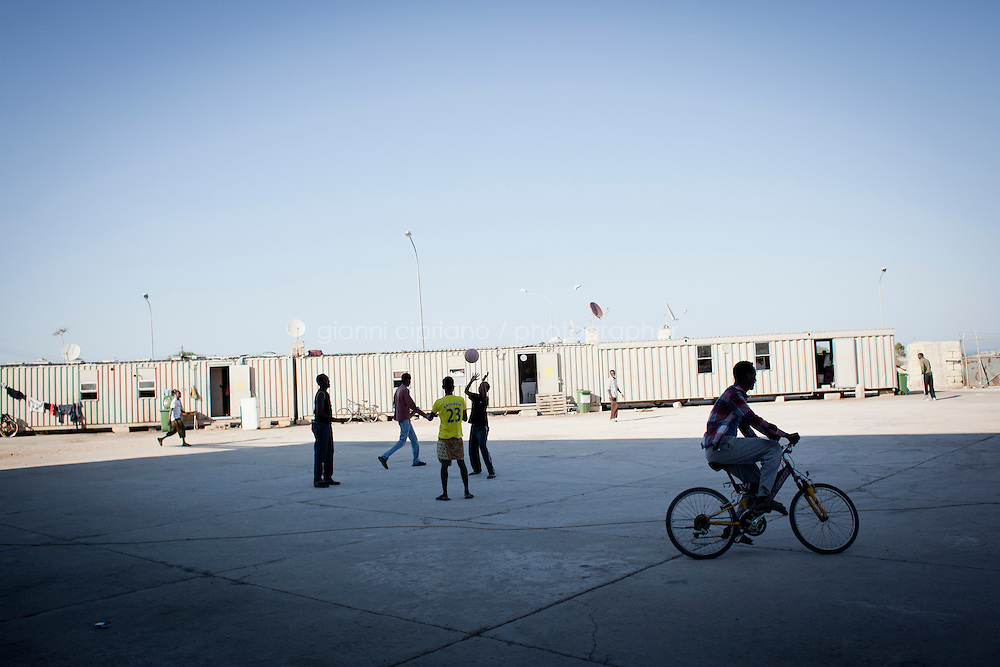 HAL FAR, MALTA - JUNE 21: Immigrants play ball and ride bikes at the Hangar Open Center in Hal Far (which translates as &quot;Rat's Town&quot;) on June 21, 2011. The Hangar Open Center is a field with an ex-aircraft hangar which includes Swiss Red Cross tents in a dark, non lit space, and external containers. The conditions are very poor and the has inflamable oil on the floor.<br /> <br /> The Open Centres in Malta serve as a temporary accomodation facility, but they ended becoming permanent accomodation centres, except for those immigrants who receive subsidiary protection or refugee status and that are sent to countries such as the United States, Germany, Poland, and others. All immigrants who enter in Malta illegally are detained. Upon arrival to Malta, irregular migrants and asylum seekers are sent to one of three dedicated immigration detention facilities. Once apprehended by the authorities, immigrants remain in detention even after they apply for refugee status. detention lasts as long as it takes for asylum claims to be determined. This usually takes months; asylum seekers often wait five to 10 months for their first interview with the Refugee Commissioner. Asylum seekers may be detained for up to 12 months: at this point, if their claim is still pending, they are released and transferred to an Open Center.<br /> <br /> <br /> Gianni Cipriano for The New York Times