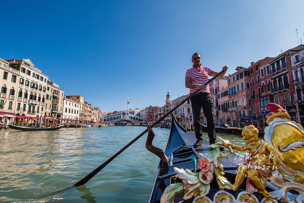Gondolier paddling a gondola in Venice, Italy, Europe