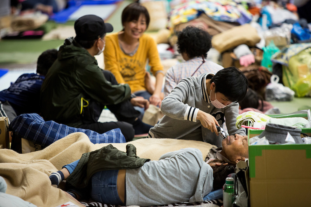 KUMAMOTO, JAPAN - APRIL 21:  A family, survived from earthquake, shave his father in the morning on April 20, 2016 in Mashiki Gymnasium evacuation center, Kumamoto, Japan. To date 45 people are confirmed dead and around 11,000 people have evacuated after an 6.5 earthquake on Thursday night and a stronger 7.3 quake on Saturday morning struck the Kyushu Island in western Japan.<br /> <br /> Photo: Richard Atrero de Guzman