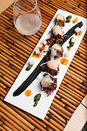 confit octopus served with a glass of sake