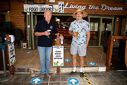 © Licensed to London News Pictures. 04/07/2020. Perranporth, UK. Father and son Bob Job and Tommy Job - owner and manager of the Watering Hole, the UK's only bar on the beach - pose with pints of beer shortly after opening time. Today marks a lift in COVID-19 restrictions, as pubs are allowed to open, whilst customers must still follow social distancing guidelines. Tens of thousands of tourists are due to arrive in Cornwall over this weekend, as overnight stays within England are also allowed. Photo credit : Tom Nicholson/LNP