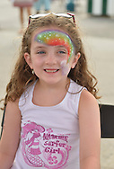 Brooklyn, New York, USA. 10th August 2013. This smiling young young girl has a sparkling rainbow painted on her face by volunteer artist Laura, during the 3rd Annual Coney Island History Day celebration.