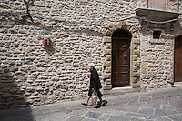 GANGI, ITALY - 30 MAY 2015: An elderly woman walks in the historical center of Gangi, Italy, on May 30th 2015. Gangi is a town with a population of 7,000 between Palermo and Catania, in the centre of Sicily, whose local administration is giving away abandoned houses of the historical centre for free. The Mayor of Gangi Giuseppe Ferrarello conceived the initiative of giving houses for free as a means to diversify the local economy - primarily dependent on agriculture and animal husbandry - by boosting tourism-related activities, and consequently counteract the phenomenon of depopulation that is typical of many small Italian towns where employment possibilities have been on a downward trajectory for years. The renovations of the assigned homes have also given work to local artisans.