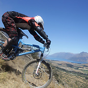 James Horan from Nelson in action during the New Zealand South Island Downhill Cup Mountain Bike series held on The Remarkables face with a stunning backdrop of the Wakatipu Basin. 150 riders took part in the two day event. Queenstown, Otago, New Zealand. 9th January 2012. Photo Tim Clayton