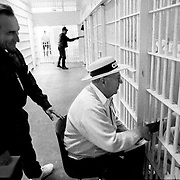 .Gust Paleologos, seated, and Richard Quick, take time in the segregated unit at Pitchess Honor Rancho to pray with an inmate as another volunteer Christian counselor greets an inmate in the background. Bill Glass is adament about his volunteers taking on a fatherly role to the inmates who often are without family.