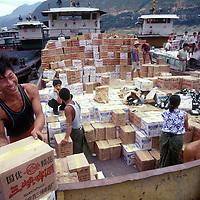 China, Sichuan Province, Wushan, Workmen unload a cargo of beer from Yangtze River boat.