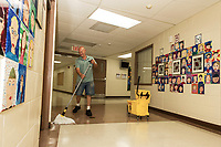 """James Moussette applies one of the six layers of wax to the floors of Elm Street School in preparation for the """"first day"""" September 4th in the Laconia School District.  (Karen Bobotas/for the Laconia Daily Sun)"""