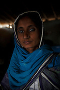 A portrait of Nusrat Babar, age 35, who's whole family enslaved for 14 years for borrowing US$143. <br /> <br /> Following the release of the Global Slavery Index by the Walk Free Foundation Pakistan is ranked 3rd worse in the world behind India and China. The Asian Development Bank estimates some 1.8 million people are slaves in Pakistan yet other estimates reach up to 4 million people, most of which toil year after year in brick kilns or sugar cane plantations. Their stories are the same; they have no-where to turn so they borrow money from a land-owner for a medical emergency or marriage dowry. The landlords pay in return for work, their labour supposed to be taken off the amount borrowed. Yet after years of no salary incredibly their amount owed is often quadrupled, the excuse being the amount they cost to feed! Many are chained, abused, raped and even killed.<br /> <br /> For years they had no where to run, no one to help but now a small local NGO called the Green Development Rural Organisation (GDRO) works to free bonded-slaves by using the law against their captives. Yet, often freed slaves end up right back where they were or risk being hunted by the landowner and forced to return. So GRDO started building villages so slaves who escape or are freed have somewhere safe to go. It now has two, whose names translate from Urdu as 'Village of the Freed' and 'Village of the Courageous', and is working on a 3rd. The land is bought and allocated to freed slave families where they can built a house and start again. Without such help the vicious cycle would continue.
