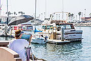 Woman Painting Boats at Oceanside Harbor