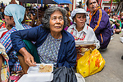"09 AUGUST 2014 - BANGKOK, THAILAND: People eat chicken and basil during the community meal for Ghost Month at the Ruby Goddess Shrine in the Dusit section of Bangkok. The seventh month of the Chinese Lunar calendar is called ""Ghost Month"" during which ghosts and spirits, including those of the deceased ancestors, come out from the lower realm. It is common for Chinese people to make merit during the month by burning ""hell money"" and presenting food to the ghosts. At Chinese temples in Thailand, it is also customary to give food to the poorer people in the community.        PHOTO BY JACK KURTZ"