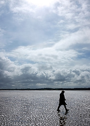 © Licensed to London News Pictures. 07/04/2012. Stiffkey, UK People walk under stormy skies on the salt marshes at Stiffkey, Norfolk today 7th April 2012.  Weather is expected to deteriorate oner the next two days Photo credit : Stephen Simpson/LNP
