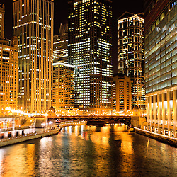 Chicago Illinois at night along the Chicago River with office buildings and Irv Kupcinet Bridge (Wabash Avenue Bridge).