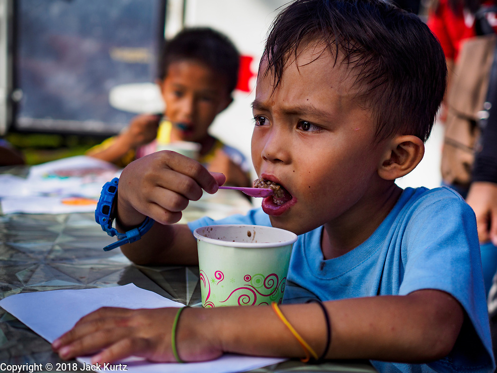 "26 JANUARY 2017 - MALILIPOT, ALBAY, PHILIPPINES: A boy who lives on the slopes of the Mayon volcano eats a ""champorado,"" a Filipino sweet of sticky rice, coconut milk and chocolate, provided by the Philippine Red Cross in the shelter in Malilipot. The volcano was relatively quiet Friday, but the number of evacuees swelled to nearly 80,000 as people left the side of  the volcano in search of safety. There are nearly 12,000 evacuees in Santo Domingo, one of the communities most impacted by the volcano. The number of evacuees is impacting the availability of shelter space. The Philippines is now preparing to house the volcano evacuees for up to three months.    PHOTO BY JACK KURTZ"