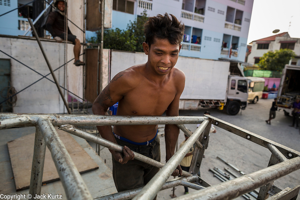 19 JANUARY 2014 - BANGKOK, THAILAND:  A member of the crew hauls stage rigging across an under construction stage before a mor lam in Khlong Tan Market in Bangkok. Mor Lam is a traditional Lao form of song in Laos and Isan (northeast Thailand). It is sometimes compared to American country music, song usually revolve around unrequited love, mor lam and the complexities of rural life. Mor Lam shows are an important part of festivals and fairs in rural Thailand. Mor lam has become very popular in Isan migrant communities in Bangkok. Once performed by bands and singers, live performances are now spectacles, involving several singers, a dance troupe and comedians. The dancers (or hang khreuang) in particular often wear fancy costumes, and singers go through several costume changes in the course of a performance. Prathom Bunteung Silp is one of the best known Mor Lam troupes in Thailand with more than 250 performers and a total crew of almost 300 people. The troupe has been performing for more 55 years. It forms every August and performs through June then breaks for the rainy season.              PHOTO BY JACK KURTZ