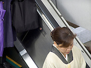 Japanese woman in traditional dress standing on an escalator