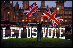 March 27, 2019 - London, United Kingdom - A protester waves Union Flags in front of the Houses of Parliament with a lit sign saying, Let Us Vote. Theresa May today announced to Tory MPs that she will resign after the next step in the Brexit negotiations if they vote for her deal. (Credit Image: © Pete Maclaine/i-Images via ZUMA Press)