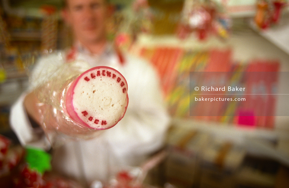 A detail of a rock and holiday souvenir seller in the Lancashire seaside town of Blackpool. Standing in his shop, we see the owner of this seaside shop on the northwest England resort where buying seaside gifts and souvenirs is ever popular by visitors and daytrippers. In 1887, sugar-boiling factory owner Ben Bullock bought some plain stick candy band had the idea of putting 'Blackpool Rock' through the centre of the rock. Now a major industry in the holiday season in Britain and many seaside towns have their versions with their own names running through the rock. Modern seaside rock is thicker, about 1 inch, and more solid than the original form. Its sugar content is nowadays a reason not to buy as much, the adverse effects on teeth from sugar and colouring by the confectionary industry being a main reason for its decline.