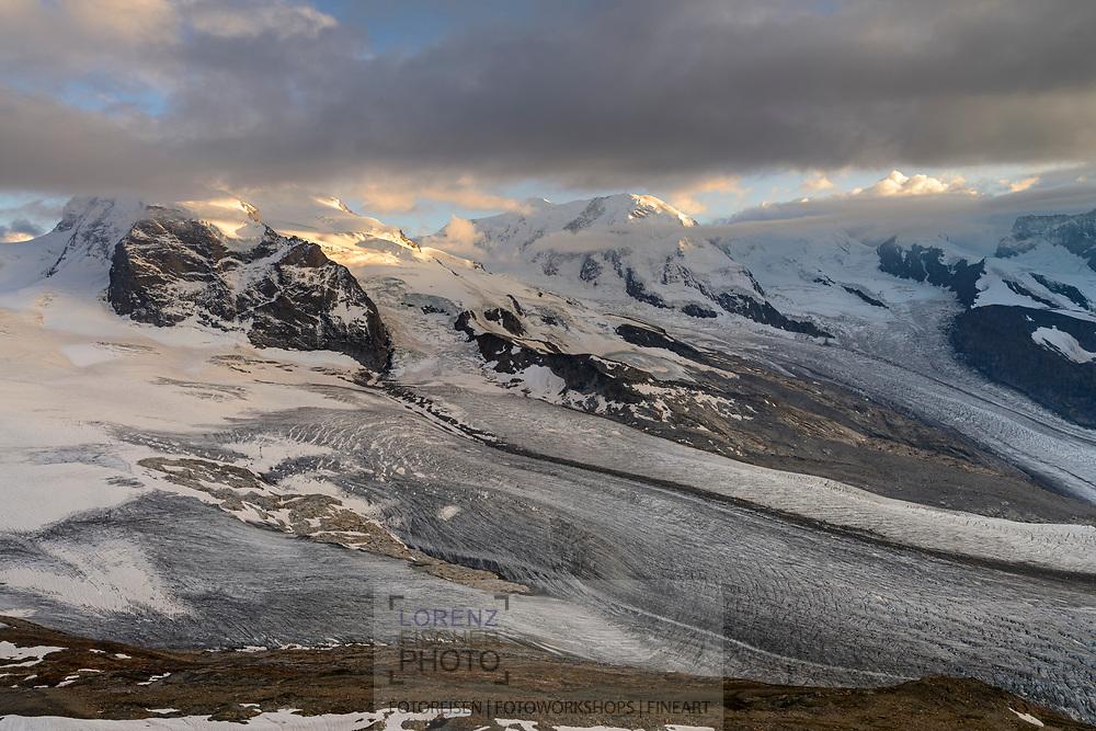 Monte Rosa mit Nordend und Dufourspitze sowie Liskamm über dem Gorner- bzw. Grenzgletscher vom Stockhorn am oberen Ende des Gornergrats in Zermatt im Kanton Wallis an einem bewölkten Abend im September